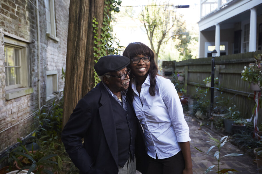 "Judge Richard Fields, affectionately known as ""The Judge"" to his family, and LaCurtia Brown embrace outside of Liz and Albert Alston's home. (Dustin Franz for NPR)"