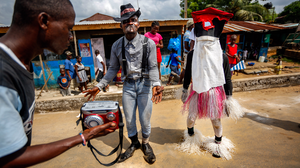 In addition to the dancing devils, there's Old Man Beggar, who also parades around on Christmas. At right is a Liberian version of Santa.