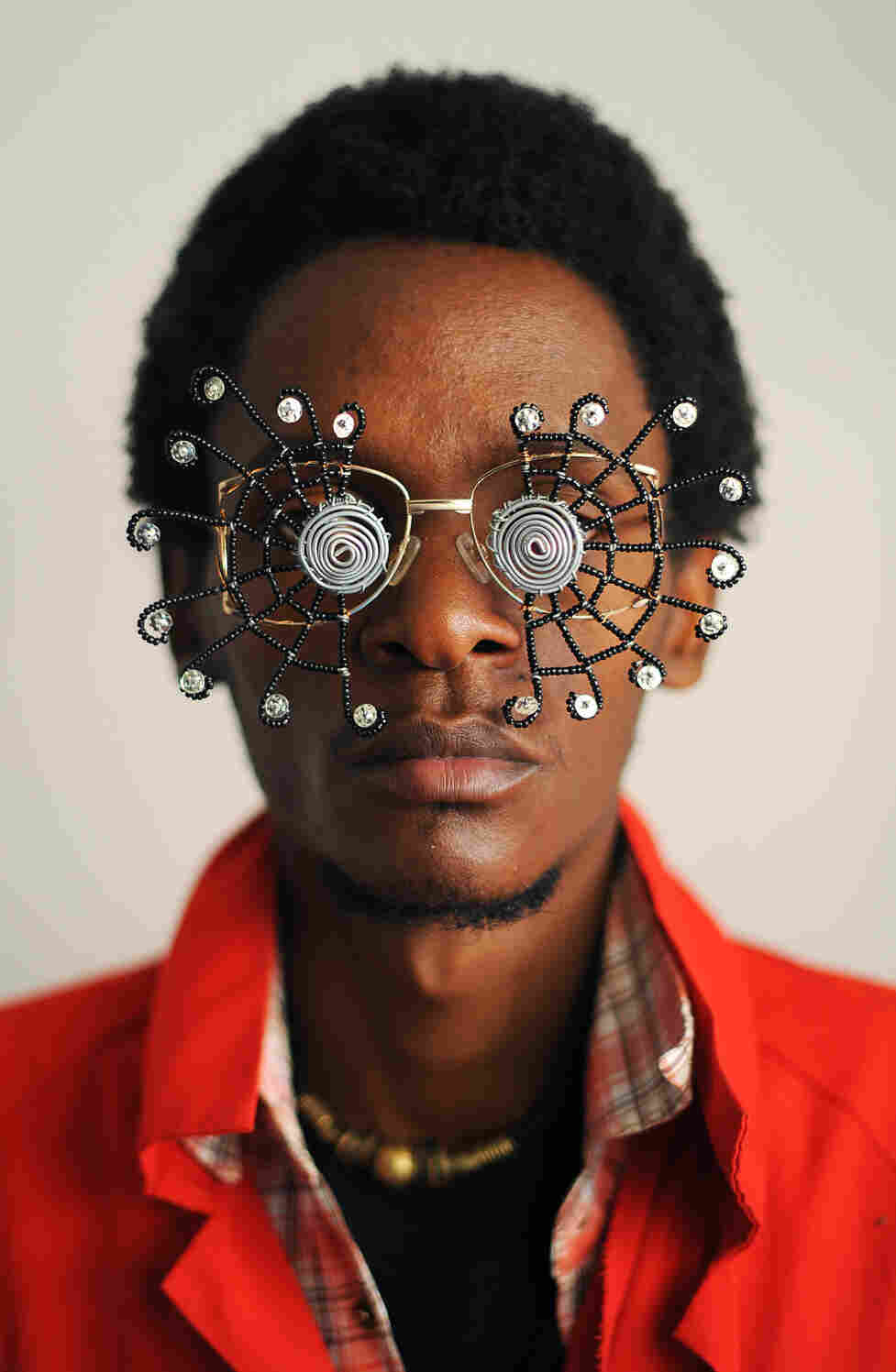 """Kenyan artist Cyrus Kabiru poses with an artwork resembling sunglasses on February 1, 2012 in Nairobi. Kabiru has created a range of artworks called """"c-stunners"""" that resemble sunglasses but have been made with objects found on the street on his way to his studio."""
