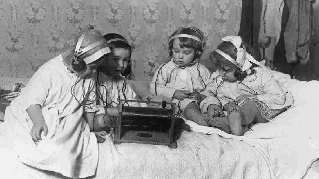 A group of young children sitting on a bed listening to the radio on headphones.