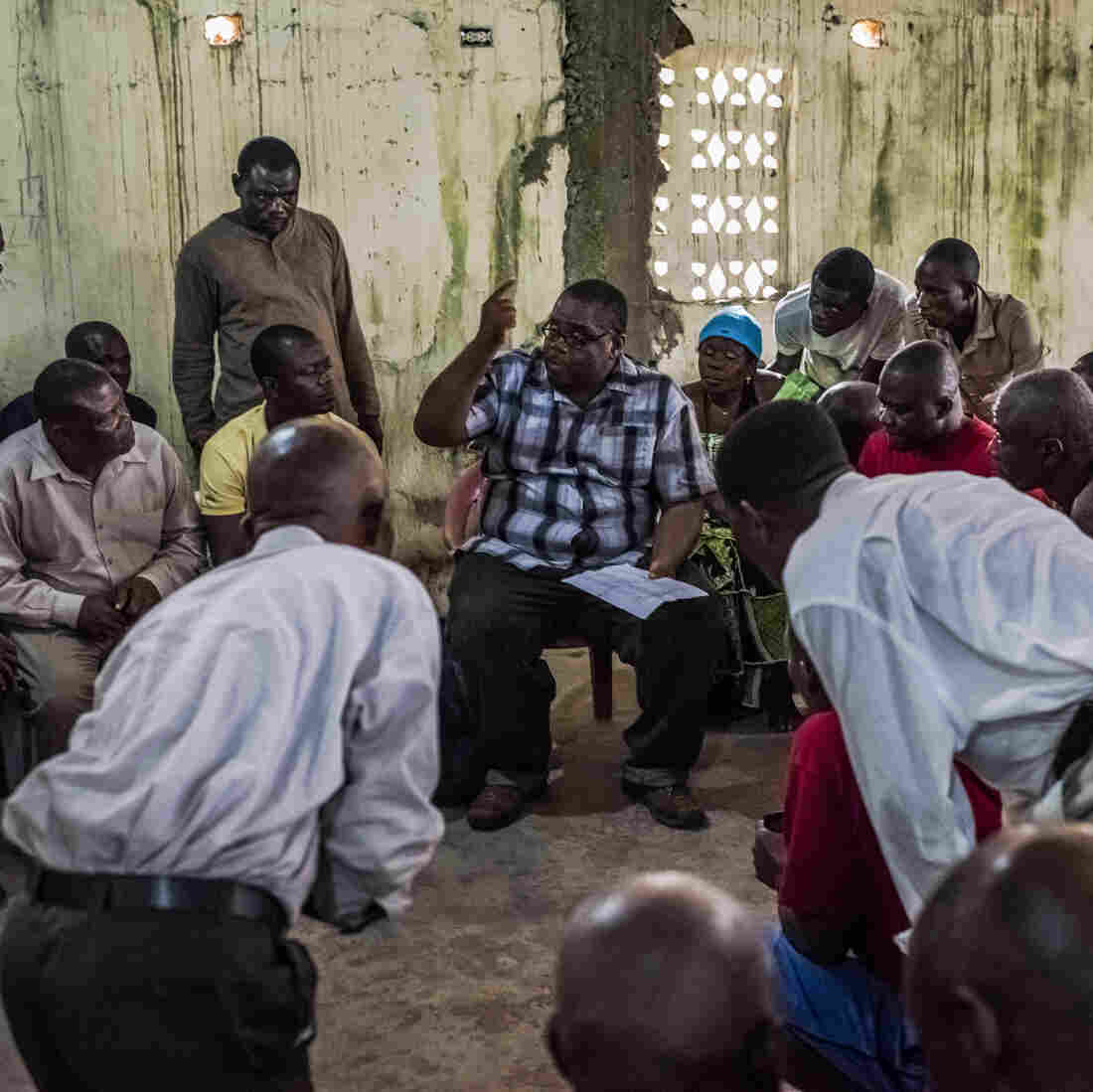Dr. Mosoka Fallah (center), an epidemiologist who investigates cases of Ebola, meets with residents of New Kru Town, a district in Monrovia, Liberia.