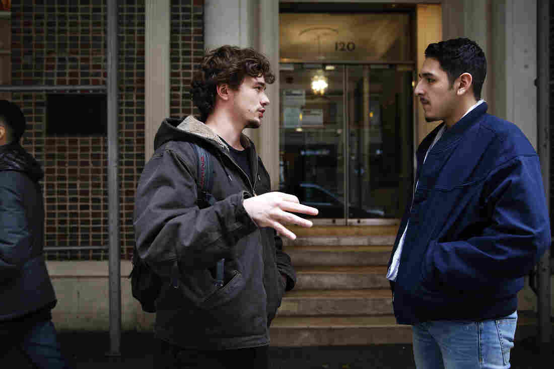 Meile talks with a fellow student outside his school's main building in Manhattan.