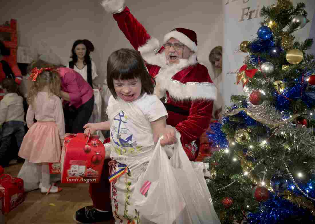 An 8-year-old girl laughs as she walks away with presents from Santa at the party. Dozens of children sang, danced and received presents during the event.