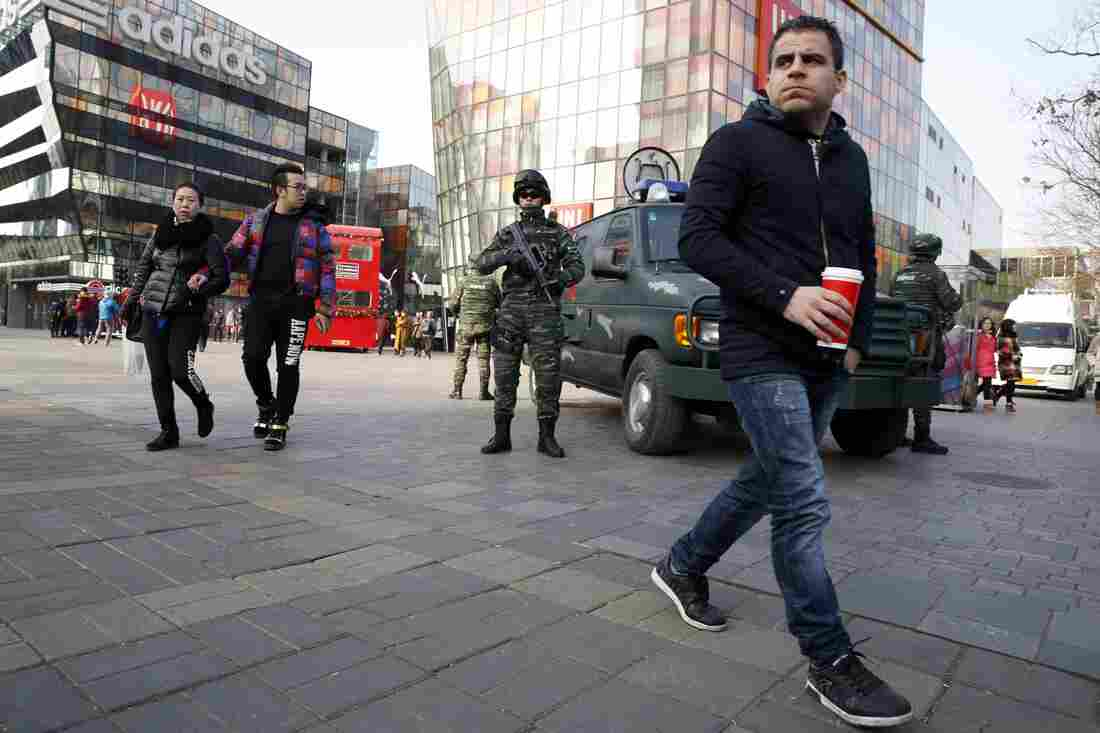 Heavily armed Chinese paramilitary police guard a popular mall in the Sanlitun district of Beijing, China, on Thursday.