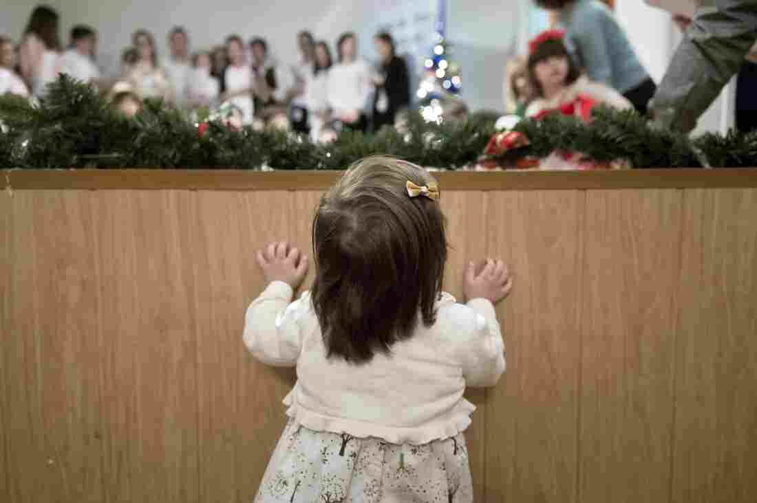 A child peers from below the stage during the party. There are tens of thousands of children with Down syndrome in Romania; they face stigma and prejudice, reports the Associated Press.