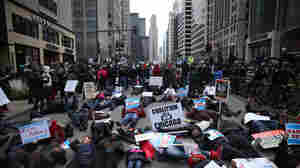 "People participate in what organizers are calling a ""Black Christmas"" protest on Michigan Avenue in downtown Chicago Thursday."