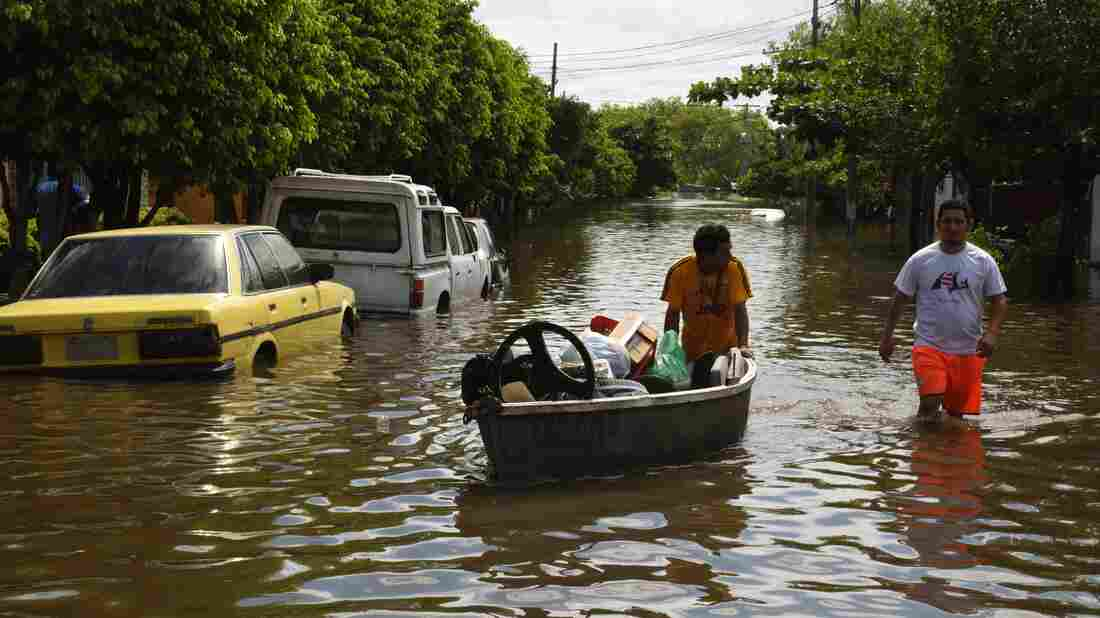 Locals recover belongings in a flooded neighborhood in Paraguay's capital, Asuncion, on Thursday.