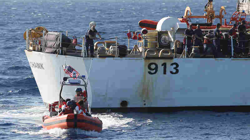 A U.S. Coast Guard crew (foreground) with six Cubans who were picked up in the Florida Straits in May. A larger Coast Guard vessel is in the background. The number of Cubans trying to reach the U.S. has soared in the past year. Many Cubans believe it will be more difficult to enter the U.S. as relations improve, though U.S. officials say there will be no rule changes in the near term.