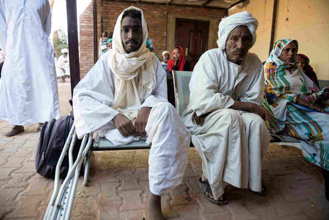 Mustafa Alnour Alhassan, 26, lost his leg to a flesh-eating fungal disease called mycetoma. Here, he sits beside his father, Alnour Alhassan, at the Mycetoma Research Center in Khartoum, the capital of Sudan.