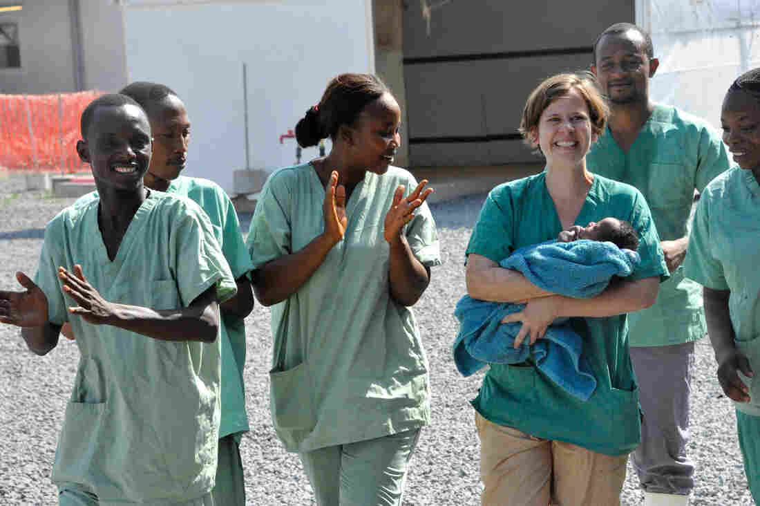 Medical workers surround 34-day-old Noubia, the last known patient to contract Ebola in Guinea, as she was released from a Doctors Without Borders treatment center in Conakry on Nov. 28.