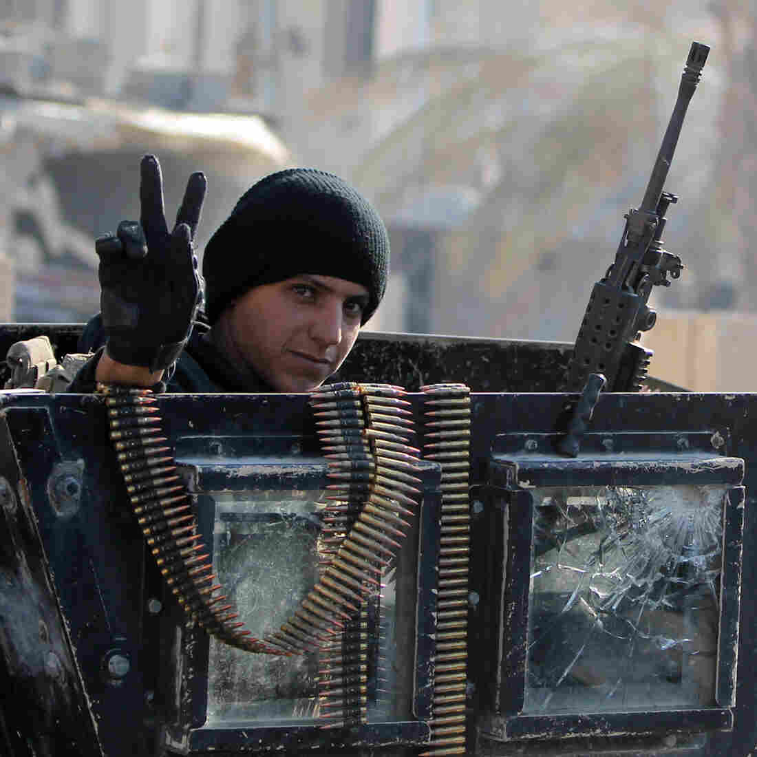 "A member of Iraq's elite counterterrorism service flashes the ""V"" for victory sign Tuesday in Ramadi, the capital of Iraq's Anbar province. Iraq's prime minister says the extremist group will be pushed out of Iraq in 2016."