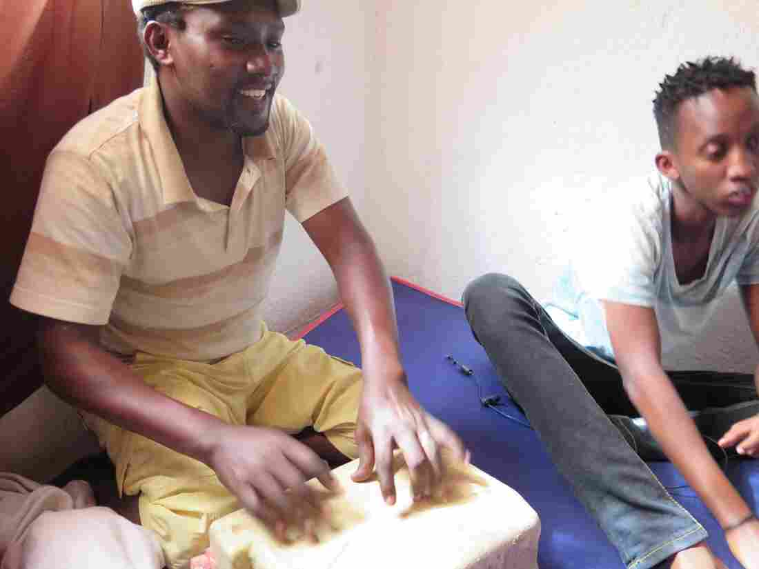 Onstage, Melodika borrows guitars and drums, but at home, Pascal Niyonzima (left) practices on plastic tubs.