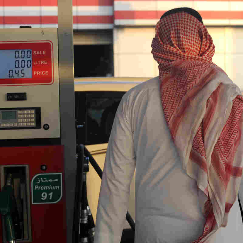 A Saudi man walks past a pump at a petrol station Monday in the Red Sea city of Jeddah. Saudi Arabia said it plans to reduce subsidies on power, water and fuel as part of new measures introduced in the face of low oil prices.