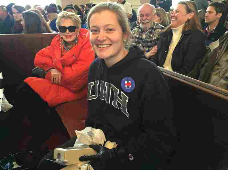 Jesse DePaolo, 21, came to  Portsmouth, N.H. with her grandmother and other relatives to hear Hillary Clinton speak. She's holding a Clinton pantsuit action figure in her hands.