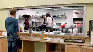 Each night, volunteers prepare a meal for the guests at the shelter, and everyone eats together.