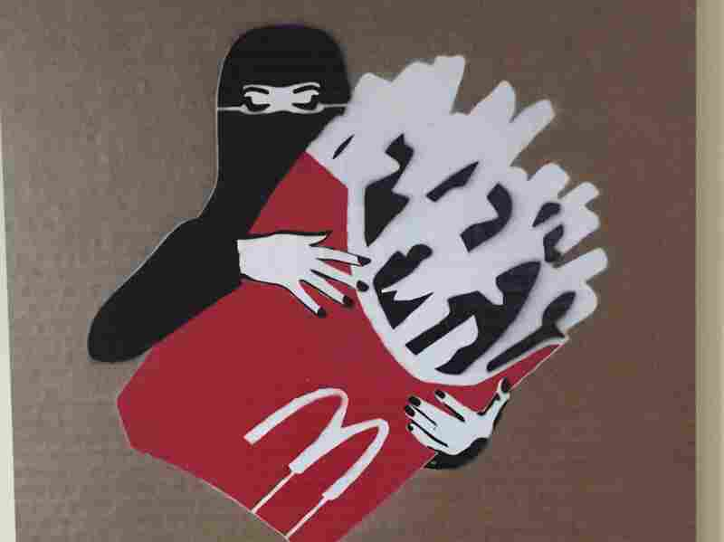 """A veiled woman with fries, from the """"LoudArt"""" exhibit in Jeddah, Saudi Arabia. The piece is by Mohammed Labban."""