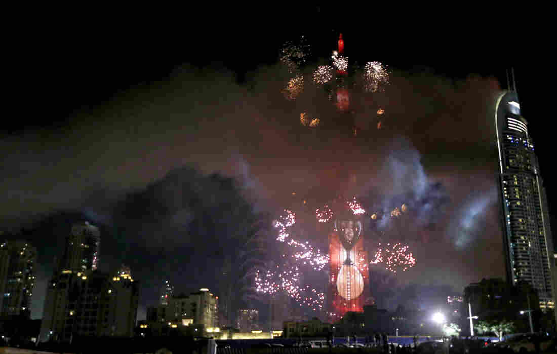 Smoke billows from the Address Downtown Hotel (right) after it caught on fire hours earlier, as a fireworks display goes off near the Burj Khalifa in Dubai on Friday.