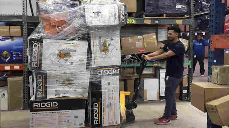 An employee drags a palette of recently returned goods through the Optoro warehouse so they can be processed.