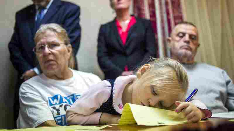 Flint, Mich., resident Jacqueline Pemberton holds her granddaughter at a press conference announcing a lawsuit against government officials in November. Pemberton is one of six plaintiffs claiming that officials violated constitutional rights by providing lead-tainted water to residents.