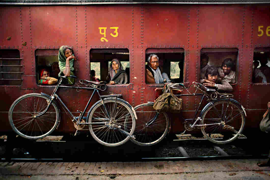 Bicycles hang on the side of a train traveling from Dacca to Peshawar, West Bengal, India. April 1993.