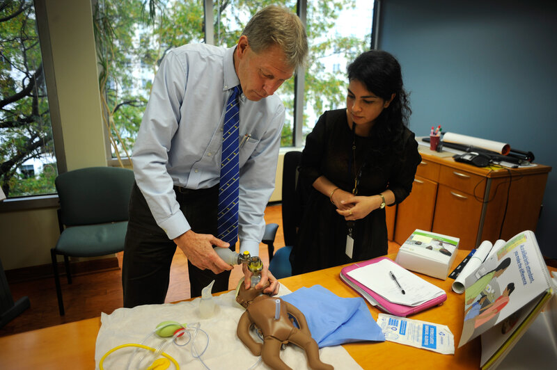 "Baby ""NeoNatalie"" waits to be saved, as Dr. Mark Hathaway gives NPR's Malaka Gharib a lesson on getting an infant to take its first breath. (Akash Ghai/NPR)"