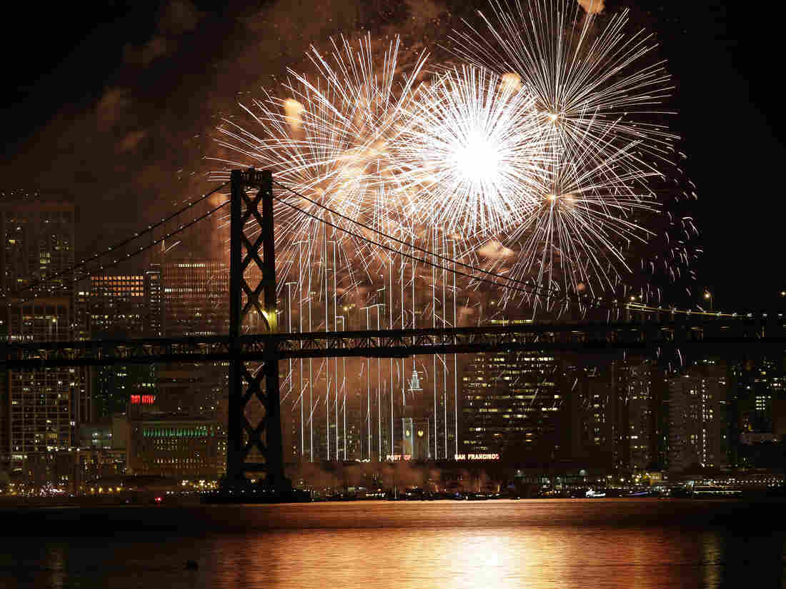 Fireworks light up the sky over the San Francisco-Oakland Bay Bridge and the city skyline as part of New Year's Eve celebrations.