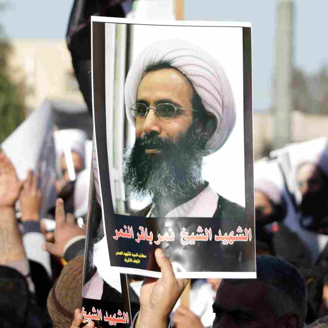 An Iraqi protester holds a poster of Shiite cleric Nimr al-Nimr, who was executed in Saudi Arabia, during a protest Monday in front of the gate of the Green Zone in Baghdad.