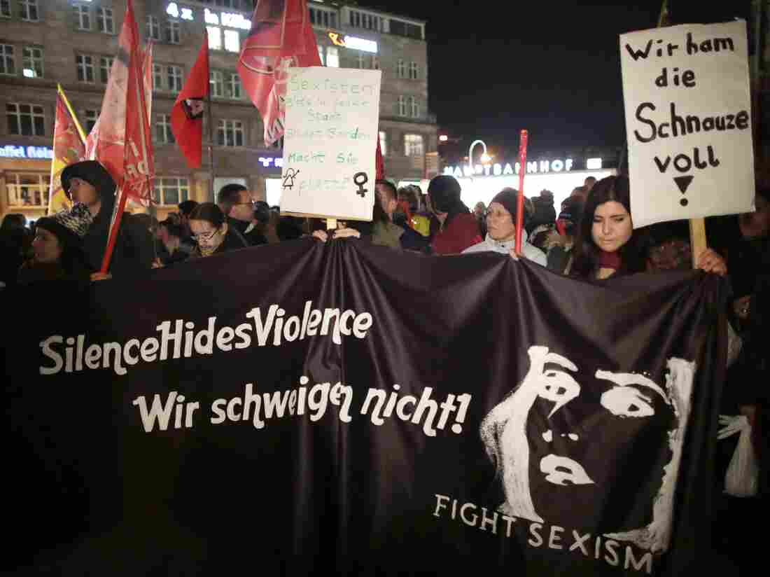 """Women protest Tuesday outside the cathedral in Cologne, with signs saying """"We are fed up"""" and """"We will not remain silent."""""""