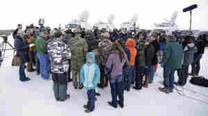 People gather as Ammon Bundy speaks with reporters during a news conference at Malheur National Wildlife Refuge headquarters on Monday near Burns, Ore. Bundy's occupation of the federal land started on Saturday.