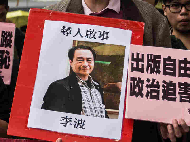 A protester in Hong Kong holds up a missing person notice on Sunday for bookseller Lee Bo. A colleague received a handwritten fax allegedly from Lee on Monday, saying he was in mainland China of his own volition. But he left his mainland travel permit at home and Hong Kong police said there was no record he'd legally crossed the border.