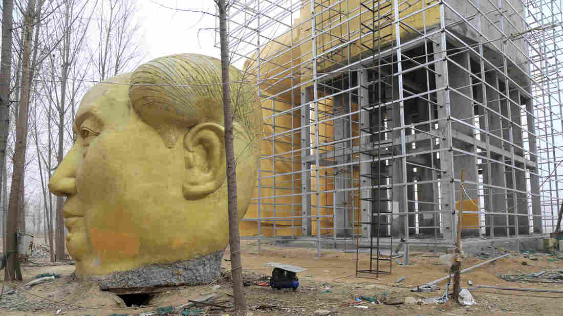 Another head in Mao's likeness is placed on the ground next to the giant statue of Mao.