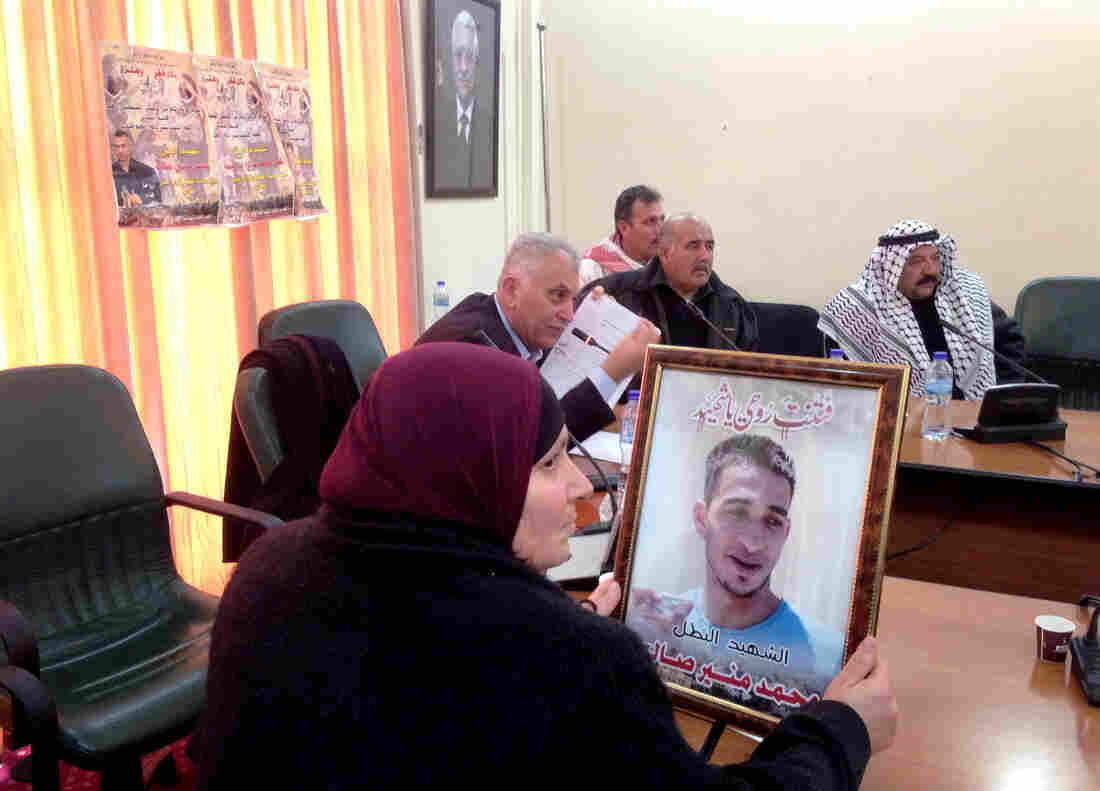 Nighma Saleh holds a portrait of her son, Mohammad Saleh, age 24 when he was killed on Nov. 17, reportedly in an armed clash with the Israeli military. She attended a meeting last week of families and activists to tell the Palestinian Authority and Israel that Palestinians refuse to comply with certain conditions for returning bodies, including a requirement to have small, private funerals.