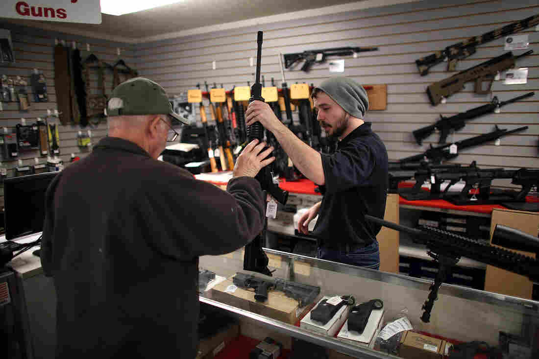 Jared Treadway, 26, a sales associate at Northwest Armory in Portland, shows a customer an AR-15 rifle Tuesday in the store's showroom.