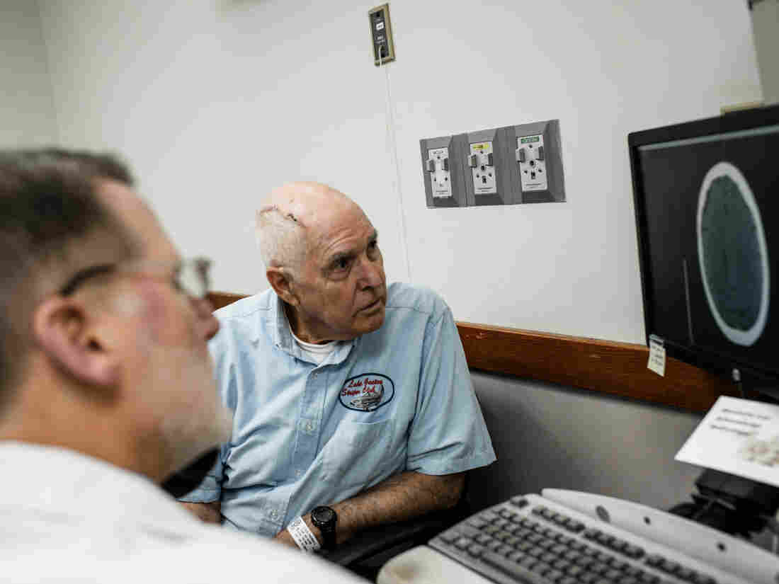 Tom Feild looks at a brain scan with his doctor at Virginia Commonwealth University Medical Center in Richmond, Va. Feild had brain surgery after experiencing a low-grade headache that wouldn't go away and difficulty driving.