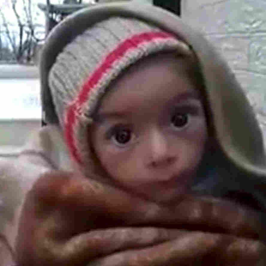 A toddler is held up to the camera in this still image taken from video said to be shot in Madaya on Tuesday. Warnings of widespread starvation are growing as pro-government forces besiege the opposition-held town in Syria.