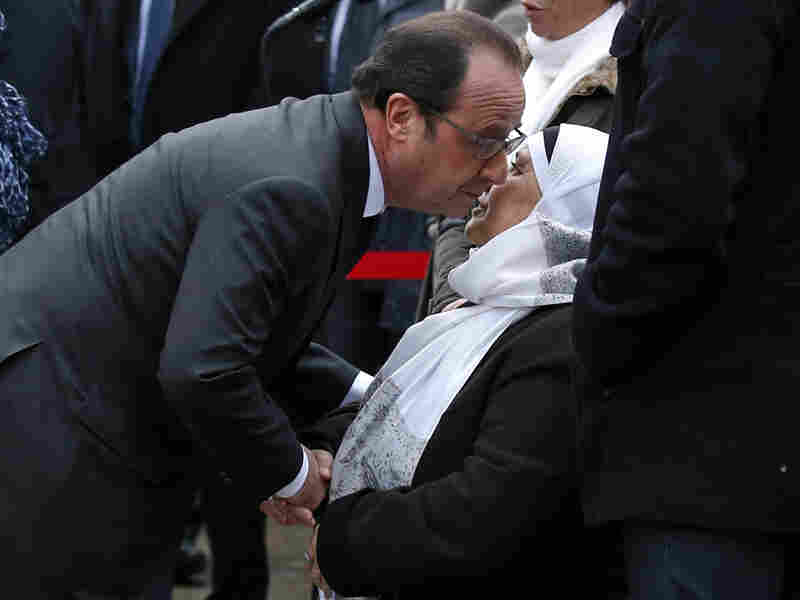 French President Francois Hollande kisses the mother of late police Officer Ahmed Merabet during commemorations in Paris on Tuesday. Hollande paid tribute to Merabet, who was killed a year ago as he tried to chase down the gunmen responsible for the Charlie Hebdo attacks.