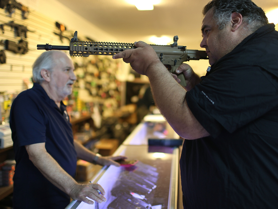 William Gordon, left, helps Steve Wrona as he looks at guns while visiting the K&W Gunworks store in Delray Beach, Fla., on Tuesday, the day President Obama announced executive action on guns. (Joe Raedle/Getty Images)