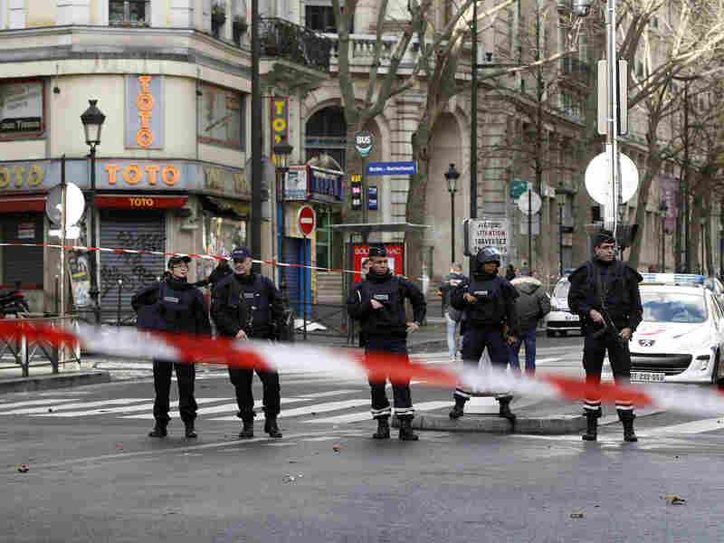 Police stand on patrol in the north of Paris on Thursday, as the city remained on edge after a man attempted to gain access to a police station while brandishing a knife. Police shot the man, who later died.