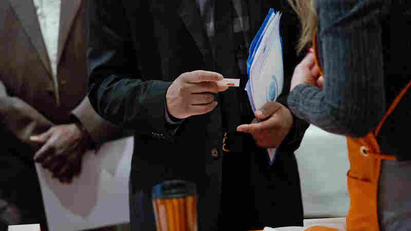 A job seeker views a business card during a Giant Job Fair last month in Detroit. During 2015, employers created 2.65 million new jobs.