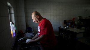 Hector Barajas washes the dishes in the Deported Veteran Support House, also known as The Bunker. Barajas has been running the shelter, seen in the bottom right photo, for about five years. At left is a collection of photos from Hector Barajas' service in the U.S. Army.
