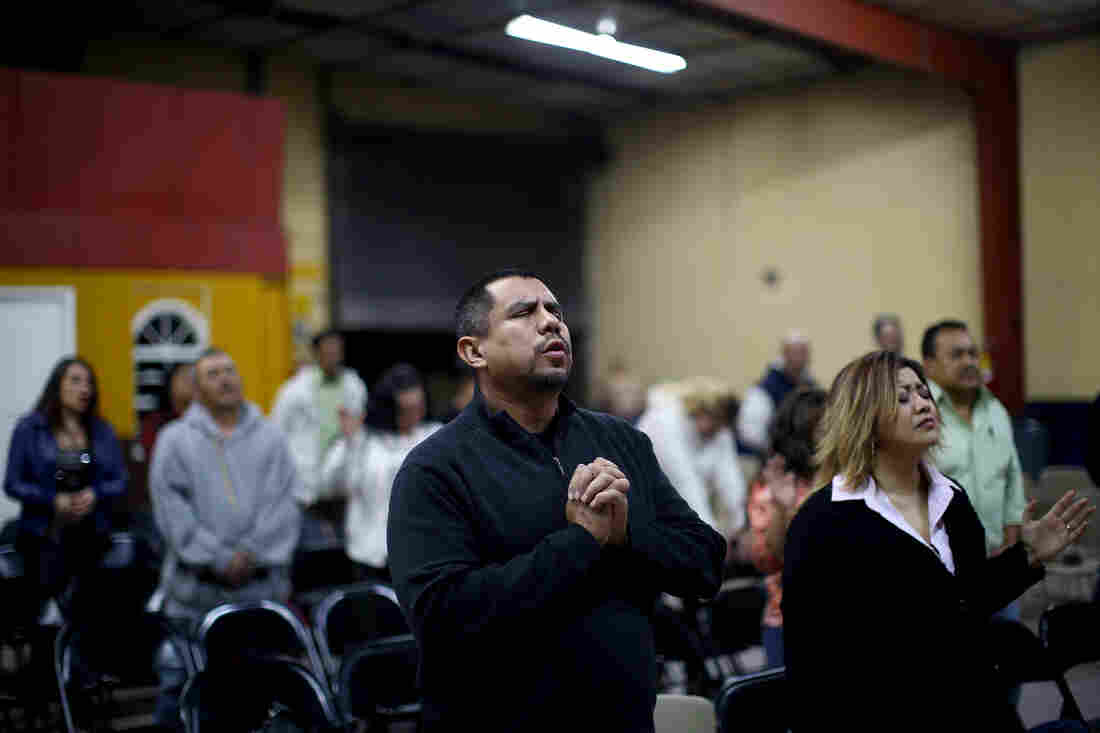 """Pastor Robert Salazar (center) prays before giving his sermon at the """"Cruising for Jesus"""" mission of Tijuana. Salazar's church also runs a men's drug-rehab shelter nearby to help deported veterans."""