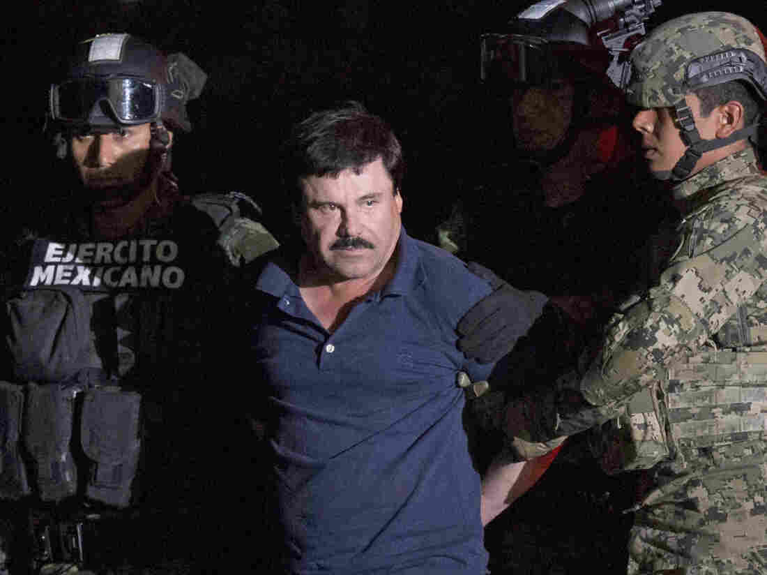 """Drug kingpin Joaquin """"El Chapo"""" Guzman, escorted by army soldiers to a waiting helicopter, at a federal hangar in Mexico City on Friday."""
