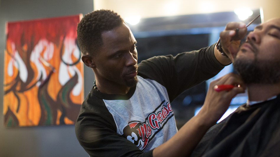 Damian Johnson, owner of No Grease Barber Shop in Charlotte, N.C., finishes up a haircut on Sam Chaney. Sam has been a client for over 10 years. (Logan Cyrus for NPR)