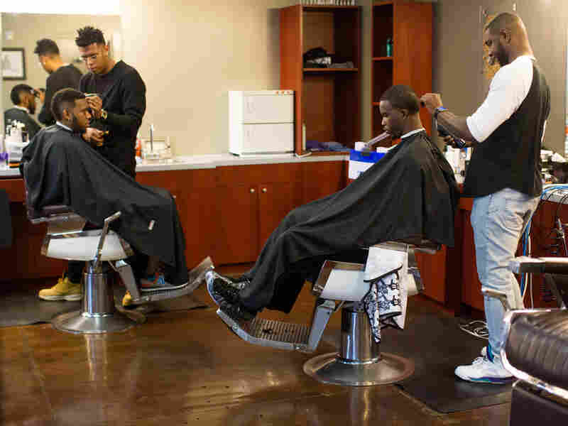 Customers get haircuts on a busy Saturday morning at No Grease Mosaic Village in Charlotte, N.C.