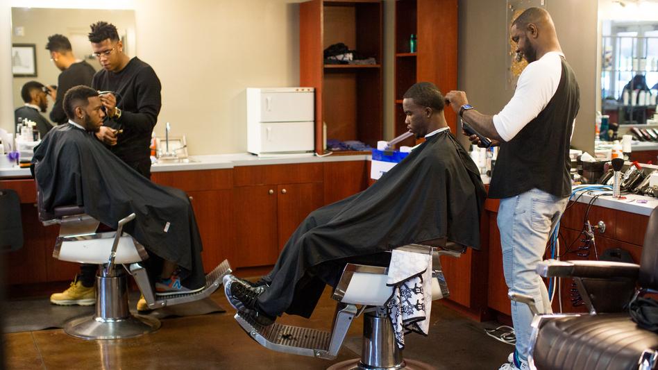 Customers get haircuts on a busy Saturday morning at No Grease Mosaic Village in Charlotte, N.C. (Logan Cyrus for NPR)