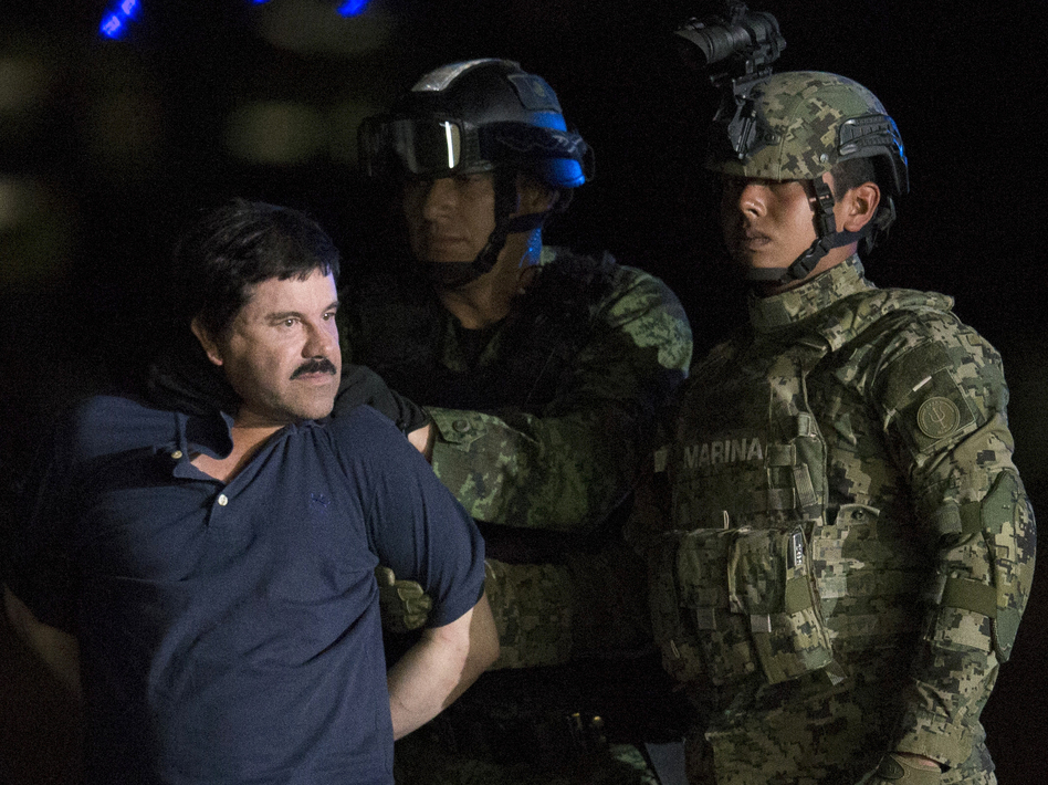 """Mexican drug kingpin Joaquin """"El Chapo"""" Guzman, escorted by army soldiers to a waiting helicopter, at a federal hangar in Mexico City on Friday. (Rebecca Blackwell/AP)"""