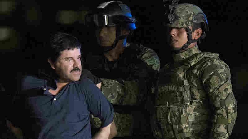 "Mexican drug kingpin Joaquin ""El Chapo"" Guzman, escorted by army soldiers to a waiting helicopter, at a federal hangar in Mexico City on Friday."