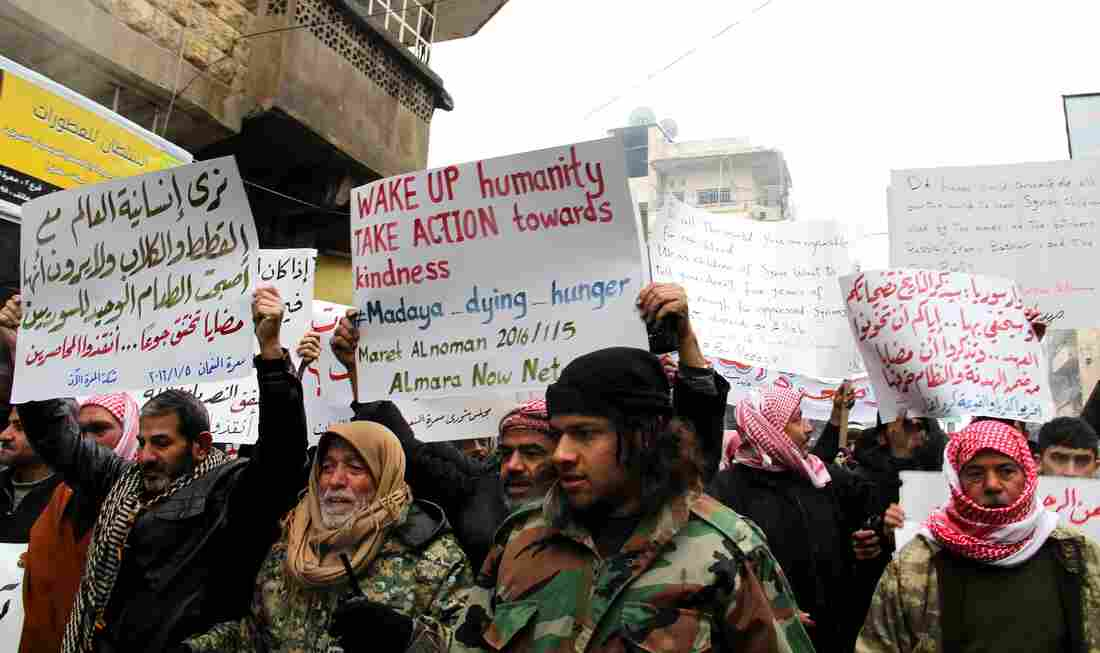 On Jan. 5, demonstrators in Maaret al-Numan, in the Idlib province of Syria, hold banners during a protest for civilians who starved to death in Madaya. Aid is expected to reach Madaya Monday. On Saturday, Maaret al-Numan, the city shown here, was hit by an airstrike that killed up to 60 people, according to the Syrian Observatory for Human Rights.