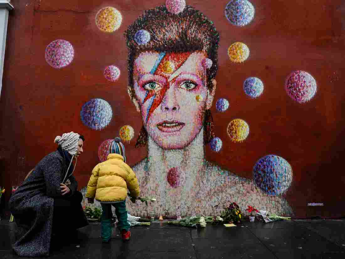 Flowers and other mementos piled up beneath a mural of David Bowie painted by Australian street artist James Cochran, aka Jimmy C, in Brixton, South London.