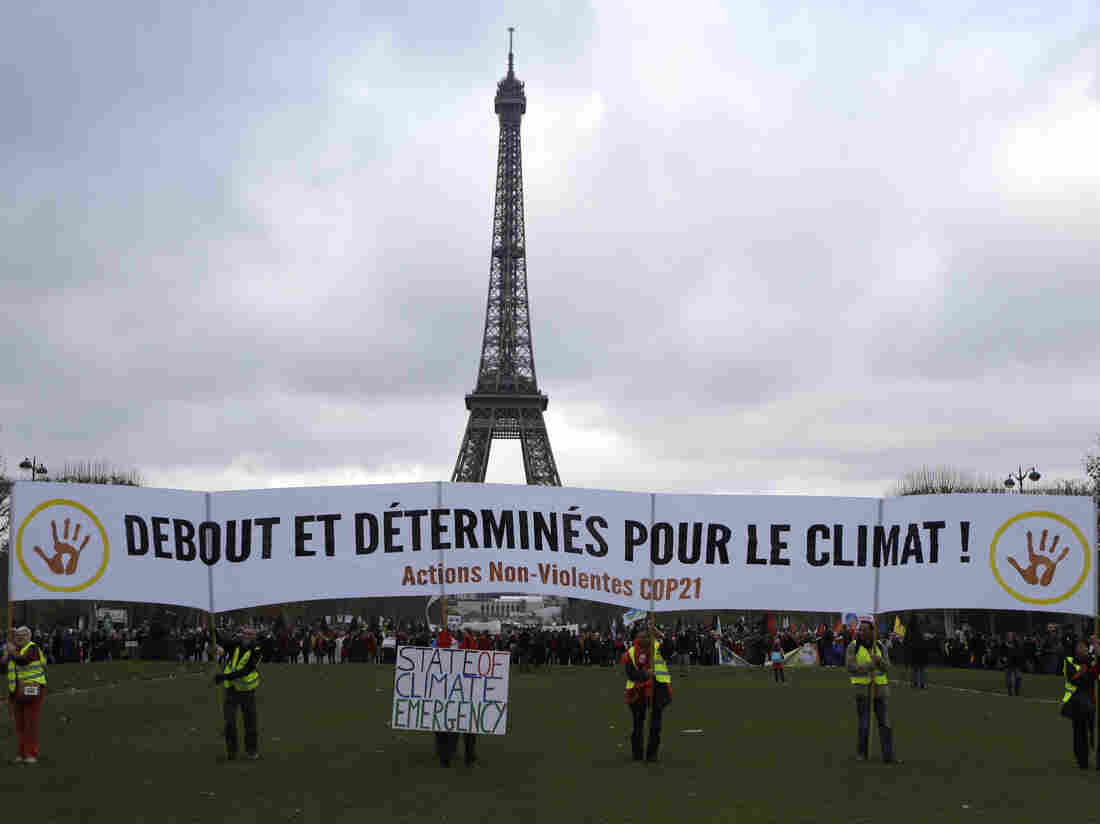 """Activists hold a banner reading """"standing and decided for climate"""" during a demonstration near the Eiffel Tower in Paris on Dec. 12, 2015, during the United Nations Climate Change Conference."""